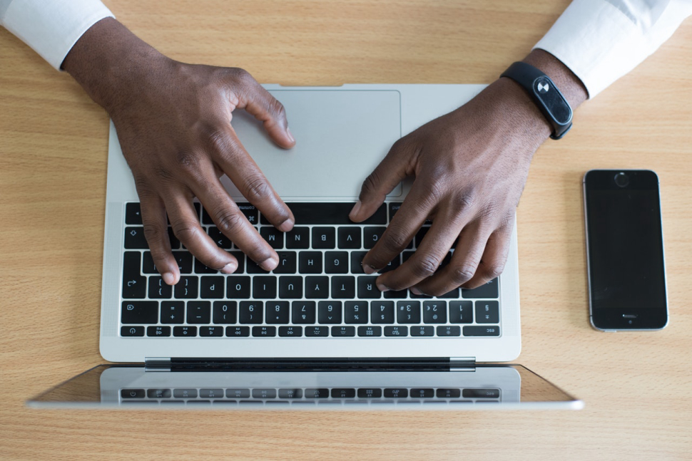 Black man typing on a laptop with a cell phone next to him.